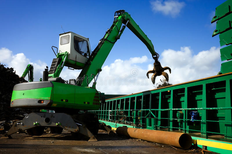 Crane loading a ship with recycling steel stock images