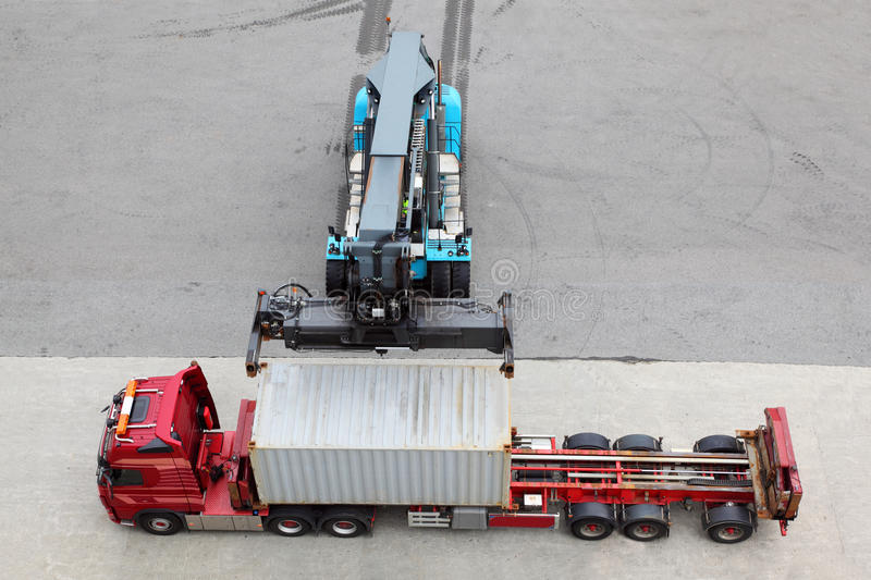 Crane moves and loads container to truck. Crane moves and loads container to big truck, view from above stock photography