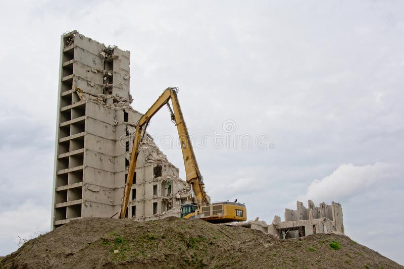 Crane next to a half demolished stripped down apartment tower stock photos
