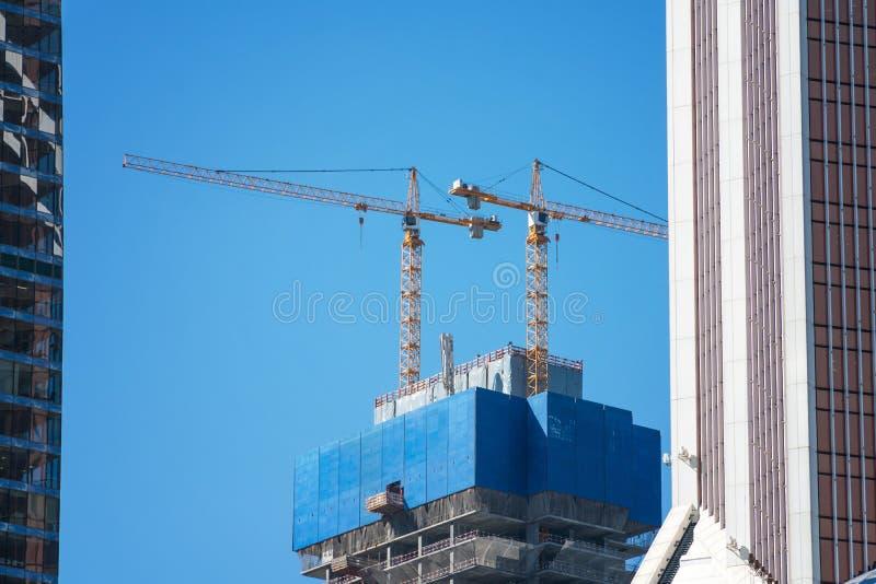 Crane o recipiente de levantamento do misturador concreto contra o céu azul imagens de stock royalty free