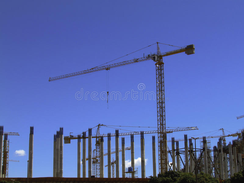 Crane operating in a construction site. Crane at construction site with columns beneath blue skies royalty free stock photo