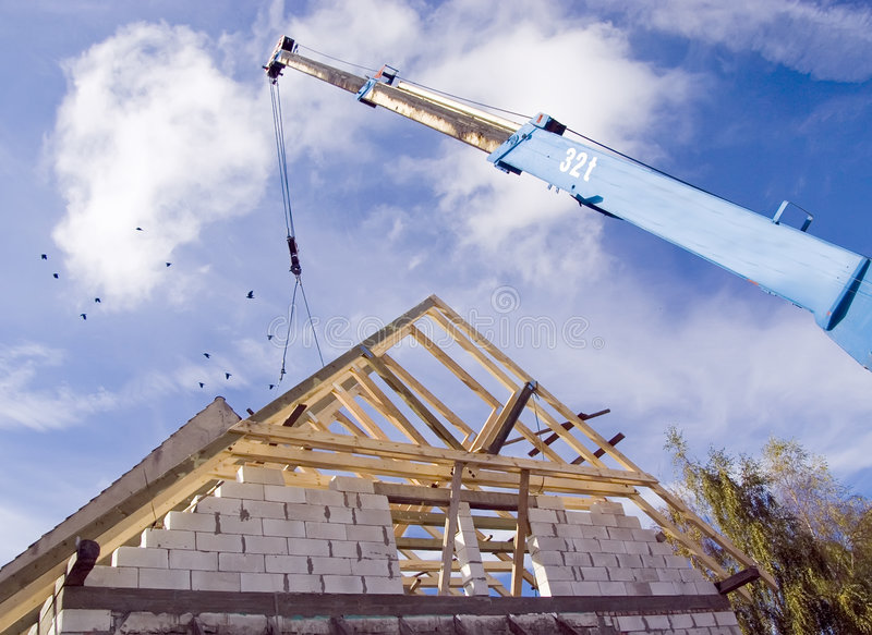 Crane operating, new roof stock image