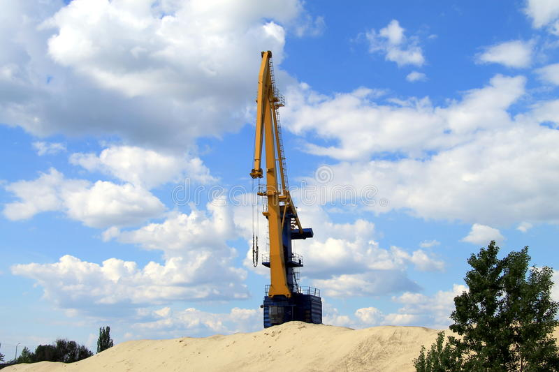 The crane in the river port. The crane in the river port on the background of beautiful clouds stock photos