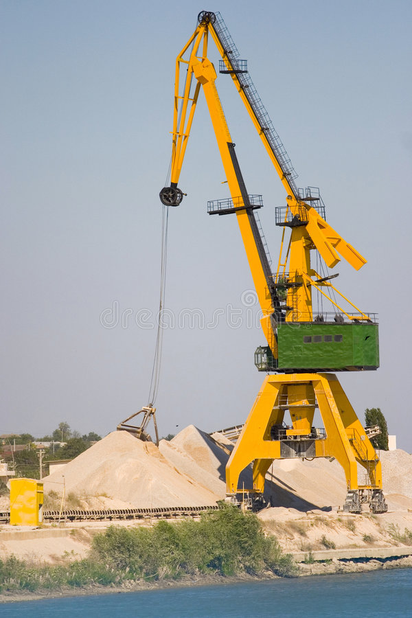 Crane on riverbank. Yellow crane on a construction site on riverbank stock images