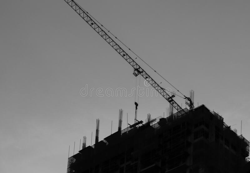 Crane on rooftop in black and white stock photography