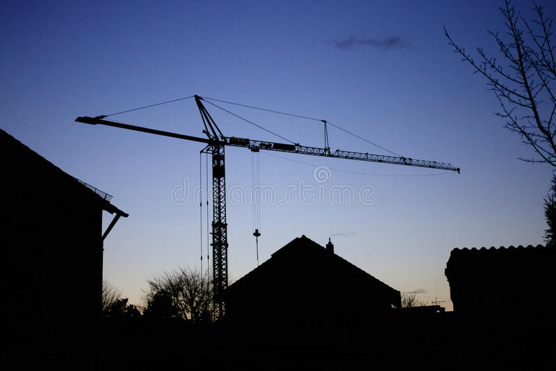 Crane Silhouette och hus royaltyfri foto