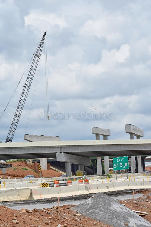A crane towers over twin bridge construction stock photography