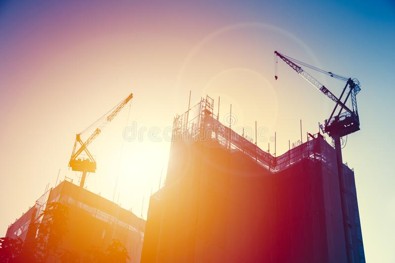 Crane with under construction building with sunset sky. stock photography