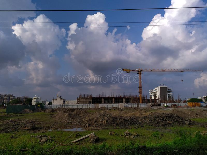 Crane at Under construction site. Giant, buildings, blue, sky, clouds, october royalty free stock photo