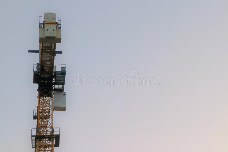 A crane at work on a building site in the city, against sky. royalty free stock photography