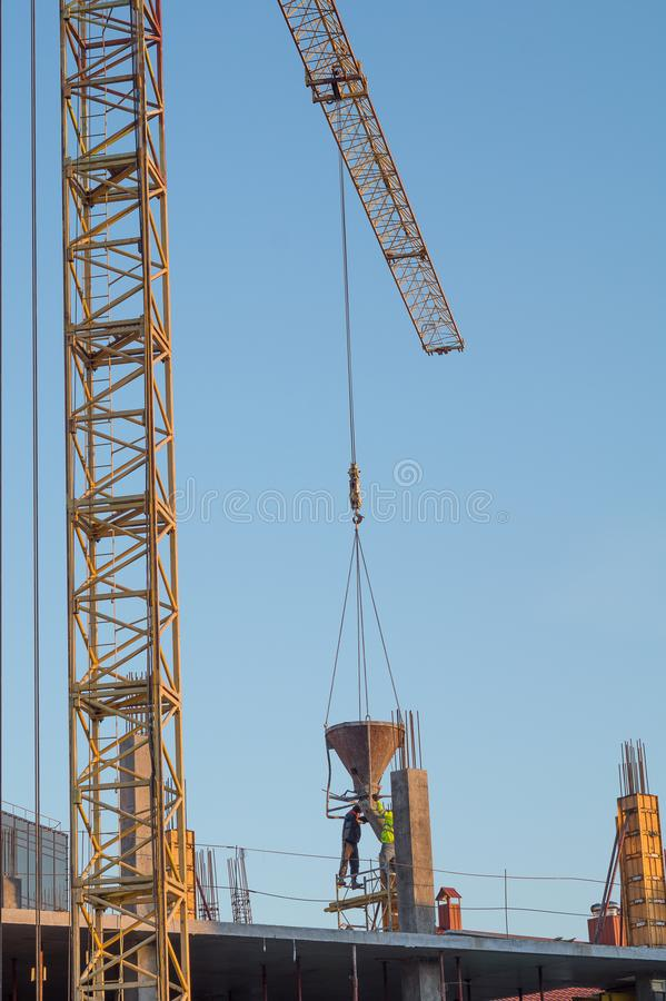 Crane Work O guindaste na construção abaixou o concreto aos trabalhadores foto de stock royalty free