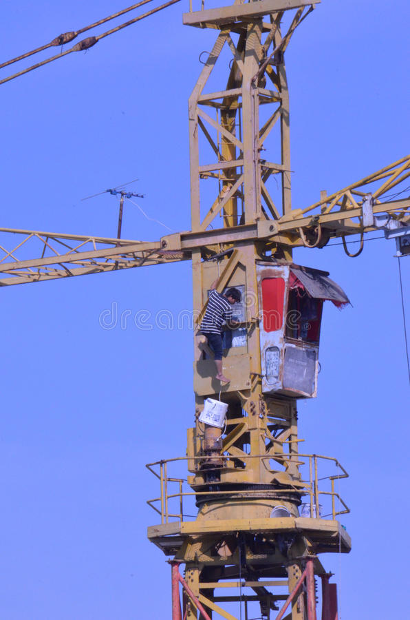 Crane workers. The tradesmen dismantling this tower crane were without any safety gear, including a harnesses to prevent falling from the structure, Pattaya royalty free stock images