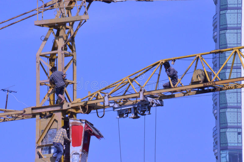 Crane workers. The tradesmen dismantling this tower crane were without any safety gear, including a harnesses to prevent falling from the structure, Pattaya stock photo