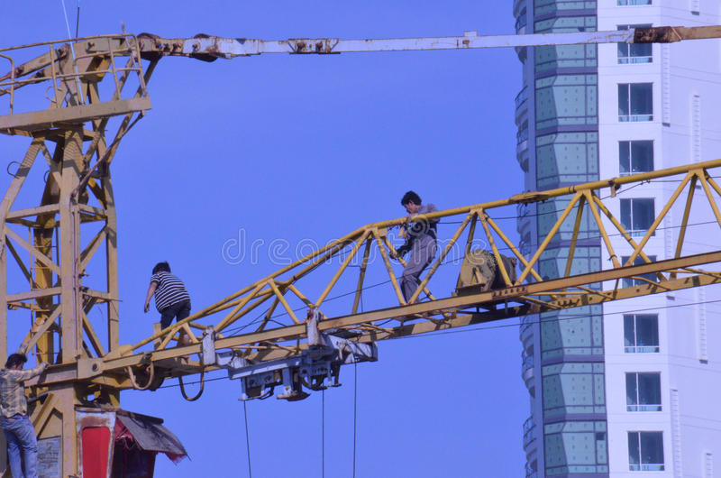 Crane workers. The tradesmen dismantling this tower crane were without any safety gear, including a harnesses to prevent falling from the structure, Pattaya stock image