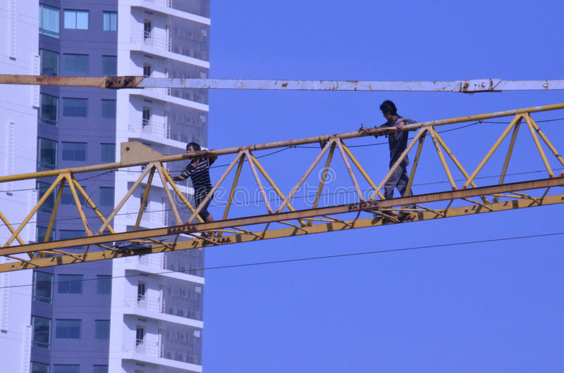 Crane workers. The tradesmen dismantling this tower crane were without any safety gear, including a harnesses to prevent falling from the structure, Pattaya royalty free stock photography