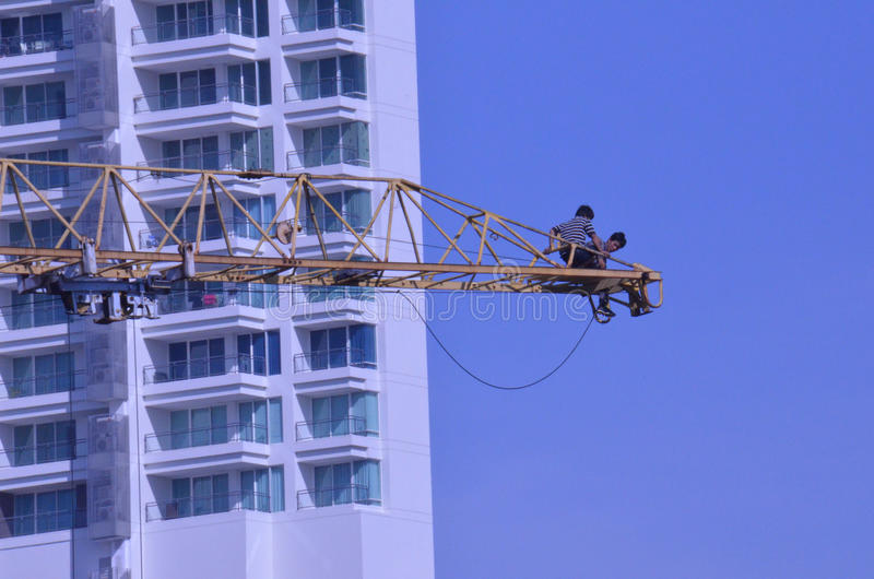 Crane workers. The tradesmen dismantling this tower crane were without any safety gear, including a harnesses to prevent falling from the structure, Pattaya royalty free stock photo
