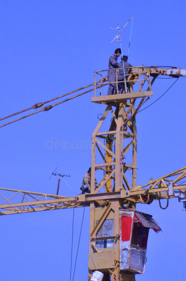 Crane workers. The tradesmen dismantling this tower crane were without any safety gear, including a harnesses to prevent falling from the structure, Pattaya royalty free stock image