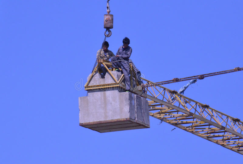 Crane workers. The tradesmen dismantling this tower crane were without any safety gear, including harnesses to prevent falling from the structure, Pattaya royalty free stock image