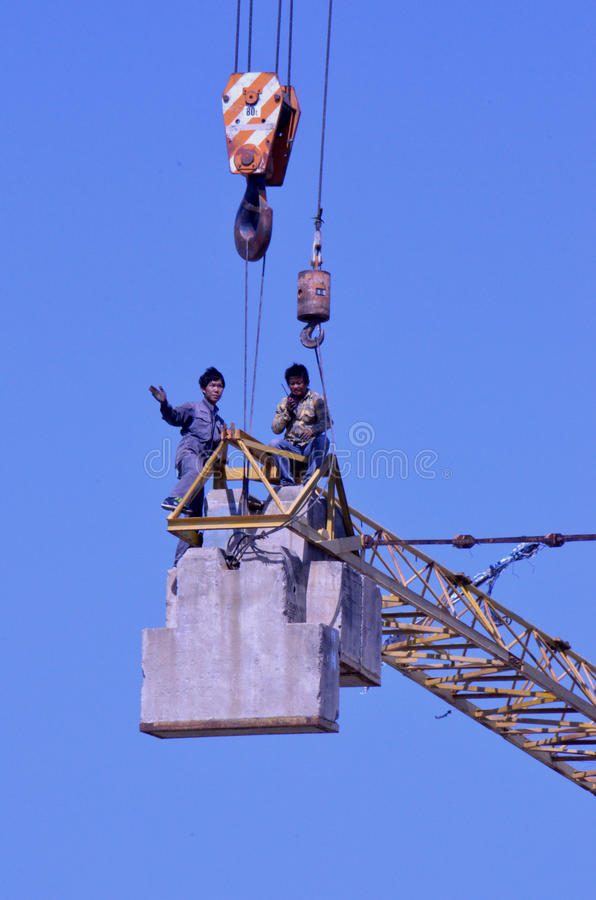Crane workers. The tradesmen dismantling this tower crane were without any safety gear, including harnesses to prevent falling from the structure, Pattaya stock images