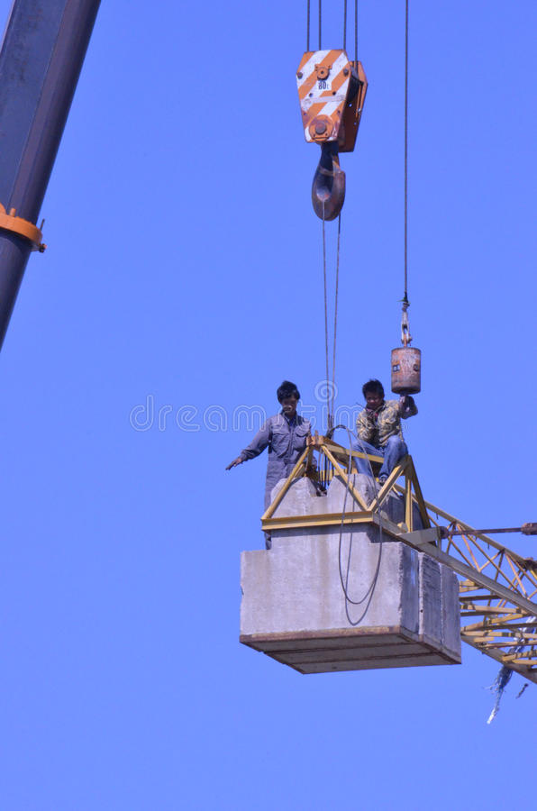 Crane workers. The tradesmen dismantling this tower crane were without any safety gear, including harnesses to prevent falling from the structure, Pattaya royalty free stock images