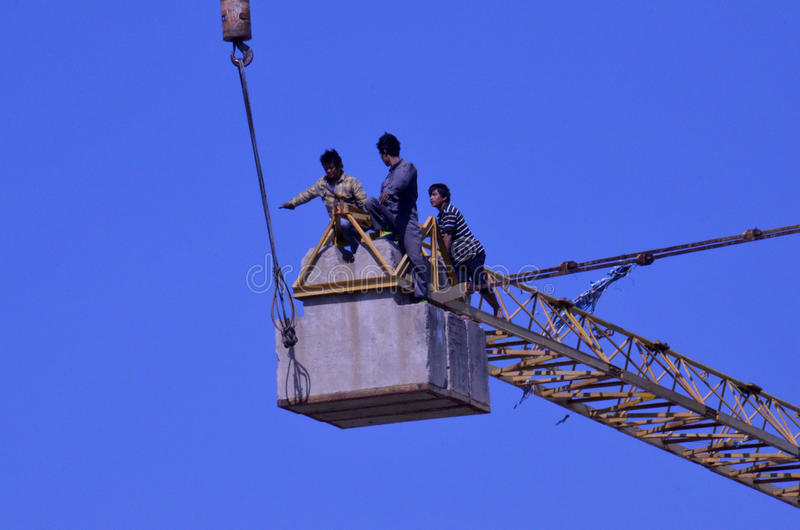 Crane workers. The tradesmen dismantling this tower crane were without any safety gear, including harnesses to prevent falling from the structure, Pattaya stock photos