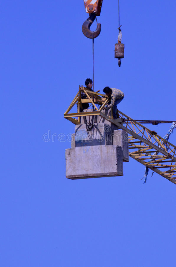 Crane workers. The tradesmen dismantling this tower crane were without any safety gear, including harnesses to prevent falling from the structure, Pattaya royalty free stock photo