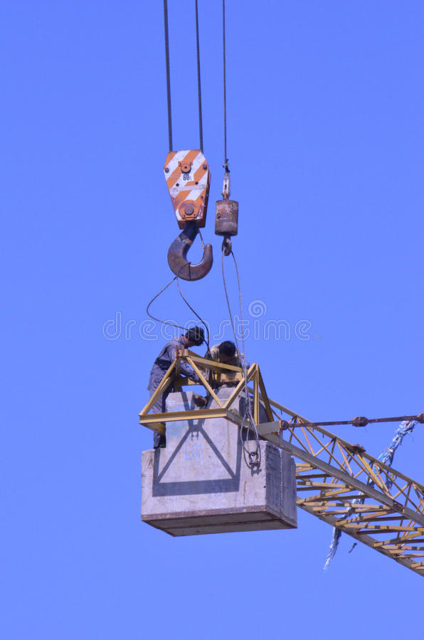 Crane workers. The tradesmen dismantling this tower crane were without any safety gear, including harnesses to prevent falling from the structure, Pattaya stock photography