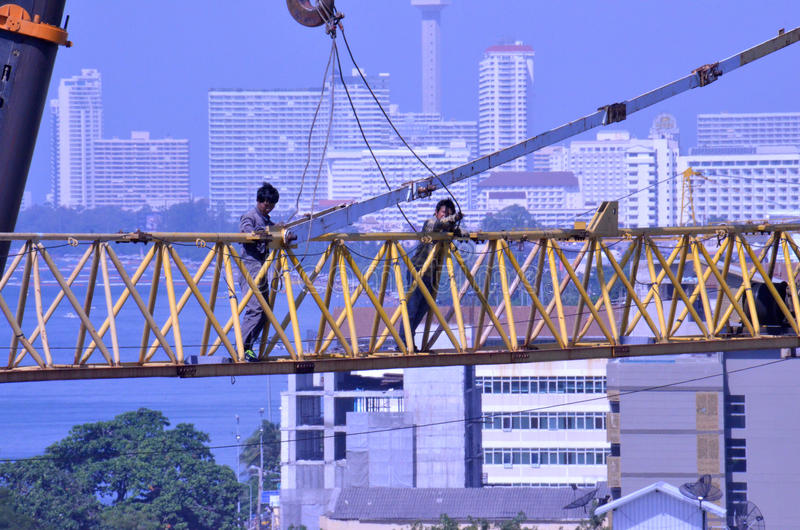 Crane workers. The tradesmen dismantling this tower crane were without any safety gear, including harnesses to prevent falling from the structure, Pattaya royalty free stock photos