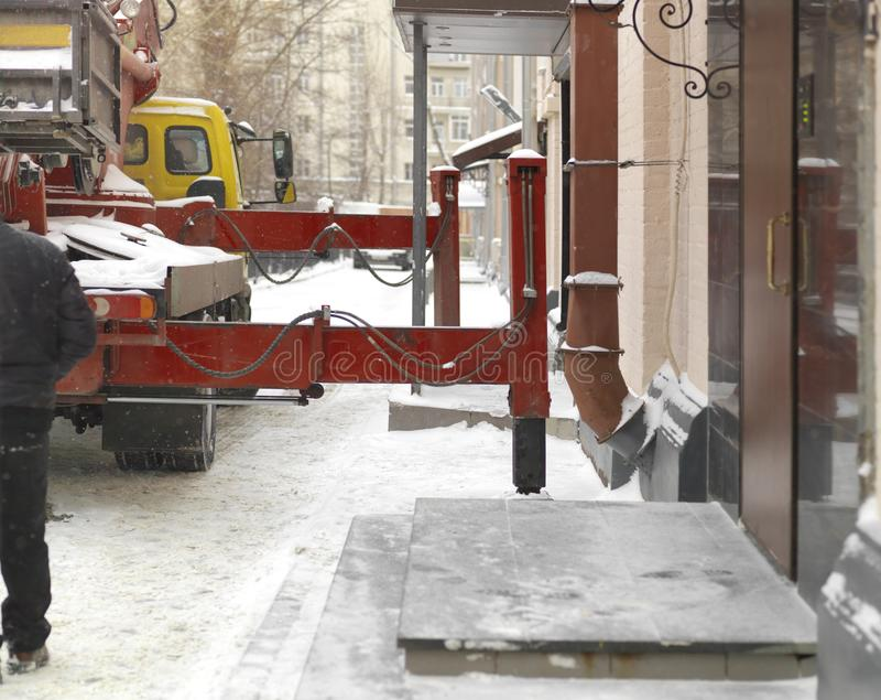 Crane Truck Working In Winter City. A crane working on the snowy street, daytime shot royalty free stock photos