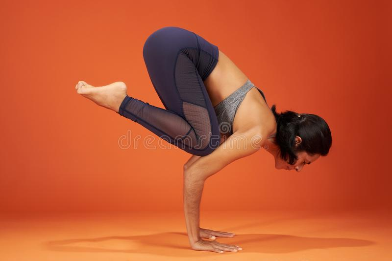 Crane yoga pose. Woman show on studio background royalty free stock images