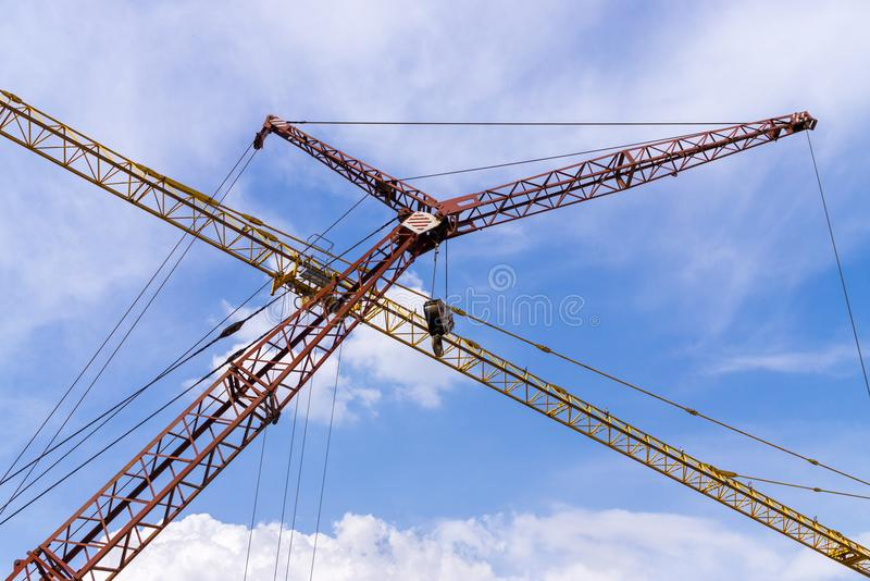 Cranes against cloudy sky stock image