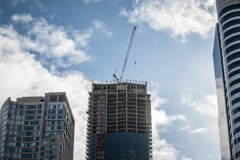 Cranes and building devices on a construction site of a skyscraper in downtown Toronto, surrounded by other high rise towers. Picture of cranes, pipes royalty free stock photography