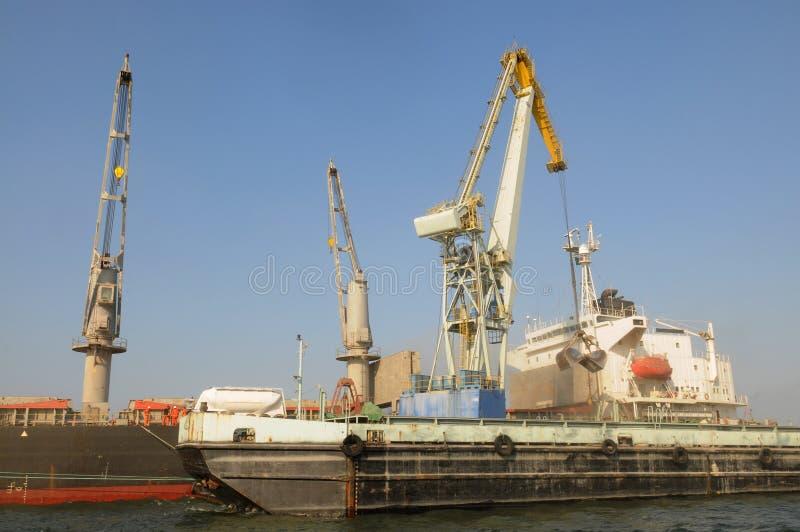 Cranes Loading Cargo Ship_Tanker Truck_Economy Stock Photography