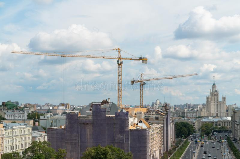 Cranes in the city landscape. Construction cranes in the urban landscape against the sky royalty free stock images