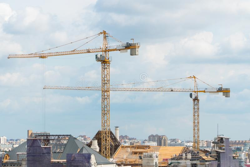 Cranes in the city landscape. Construction cranes in the urban landscape against the sky stock photos