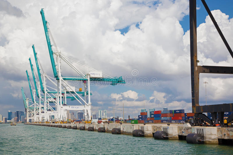Cranes and containers in Miami harbor. Miami, Florida, USA - August 2015: huge cranes in Miami harbor and many multicolored containers on the dock. No people royalty free stock photos