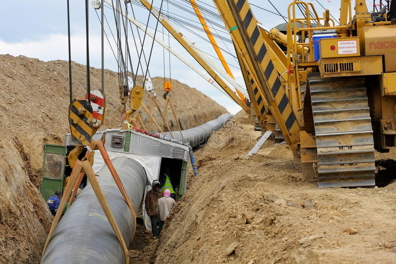 Cranes laying gas pipeline and welding cabin. Construction of an international gas pipeline Gazela going from Russia to Germany, supplying Germany by natural gas