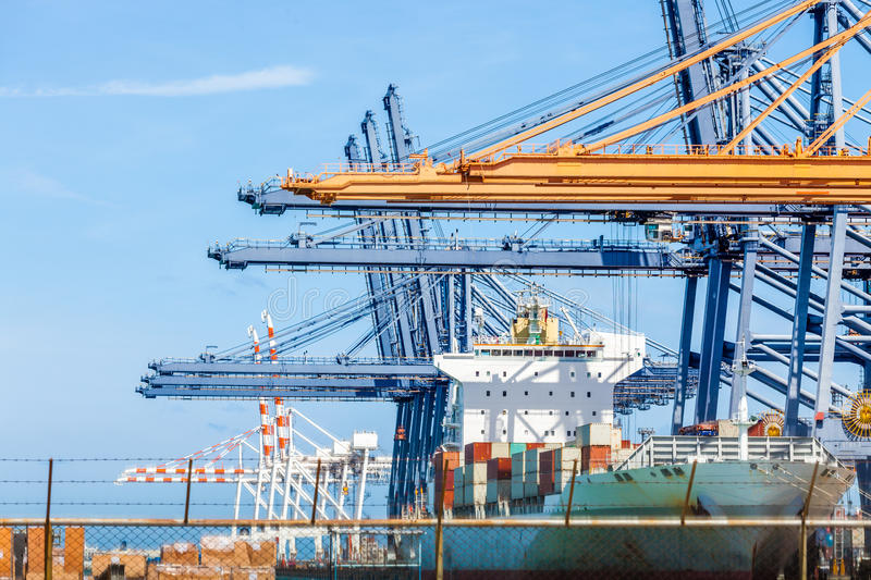 Cranes load containers on a large transport ship at trade port. Cranes load containers on a large transport ship with clear blue sky background at trade port royalty free stock photography