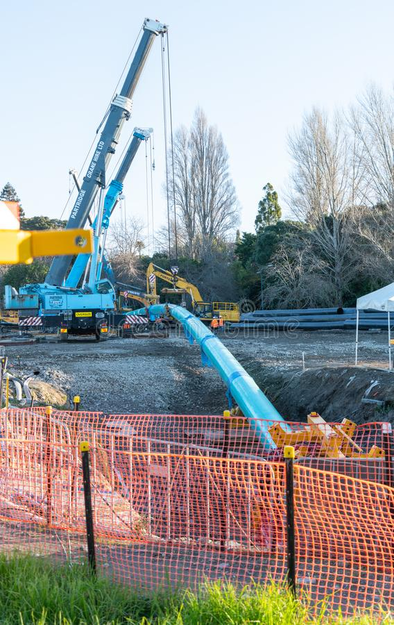 Cranes and plant at Memorial Park Southern Pipeline project base. TAURANGA, NEW ZEALAND - JULY 23 2018; Cranes and plant at Memorial Park Southern Pipeline royalty free stock photos