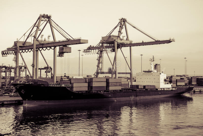 Container Ship with Port Cranes. Use of a sepia wash across this photo gives it an aged look of an old industrial dock full of activity loading a cargo ship stock photos