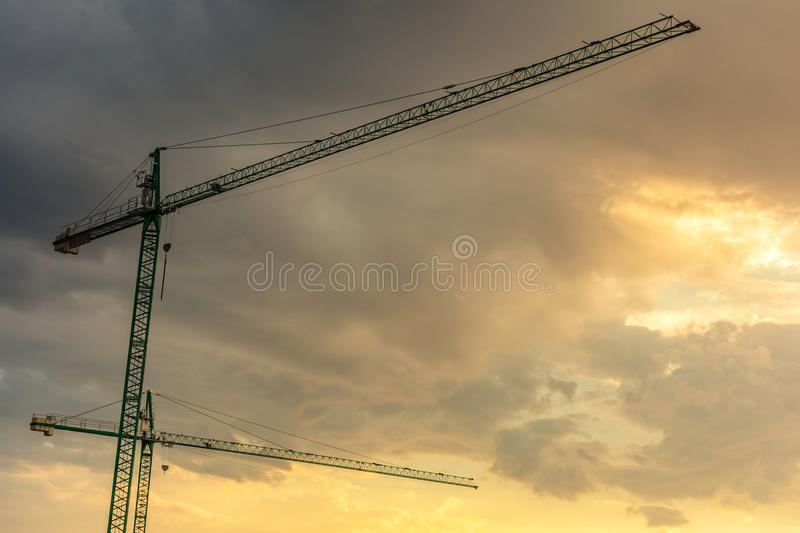 Cranes in the sunset, end of the workday in the work royalty free stock photos