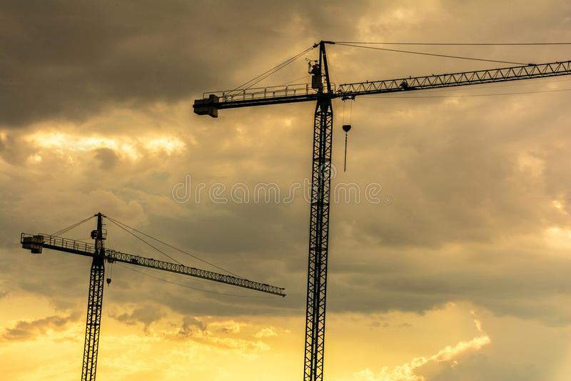 Cranes in the sunset, end of the workday in the work stock images