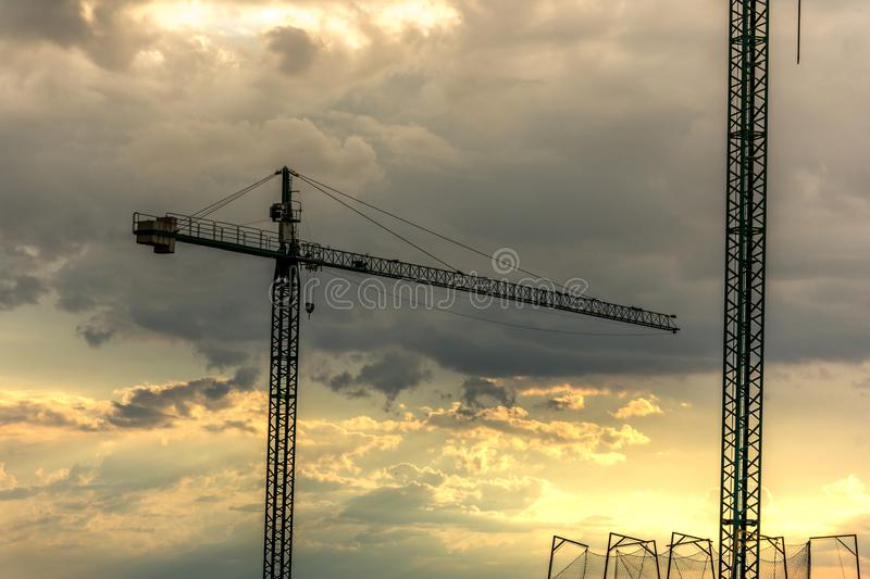 Cranes in the sunset, end of the workday in the work stock photography