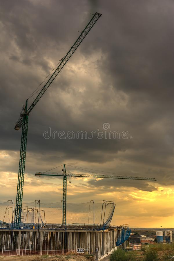 Cranes in the sunset, end of the workday in the work royalty free stock images
