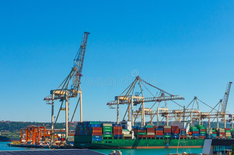 Cranes unloading a ship in a harbor. Koper, Slovenia - 27.07.2019. Cranes unloading a ship in a harbor, Koper, Slovenia 27.0719, shipping, heavy, machine stock photo