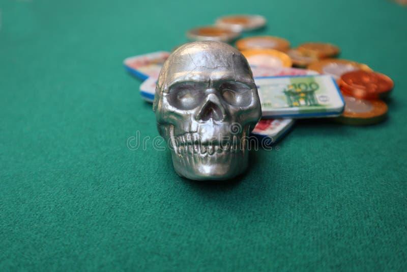 Cranio con soldi sulla tavola verde fotografia stock