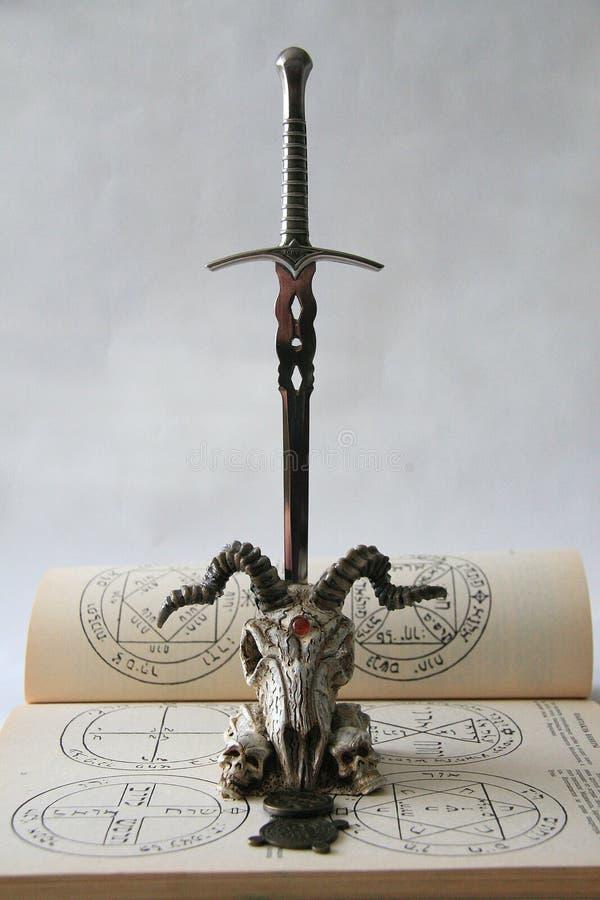 Cranio con una lama e un pentagram fotografia stock