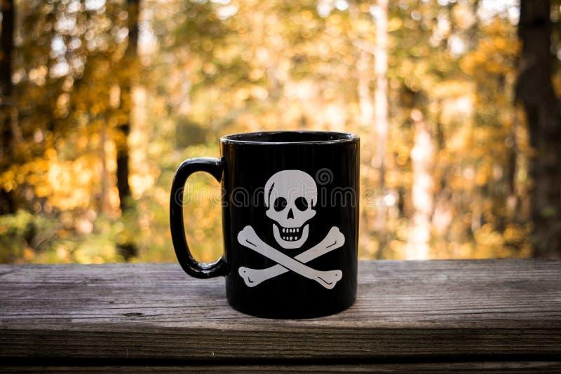 Cranio e tazza da caffè di tibie incrociate fotografie stock