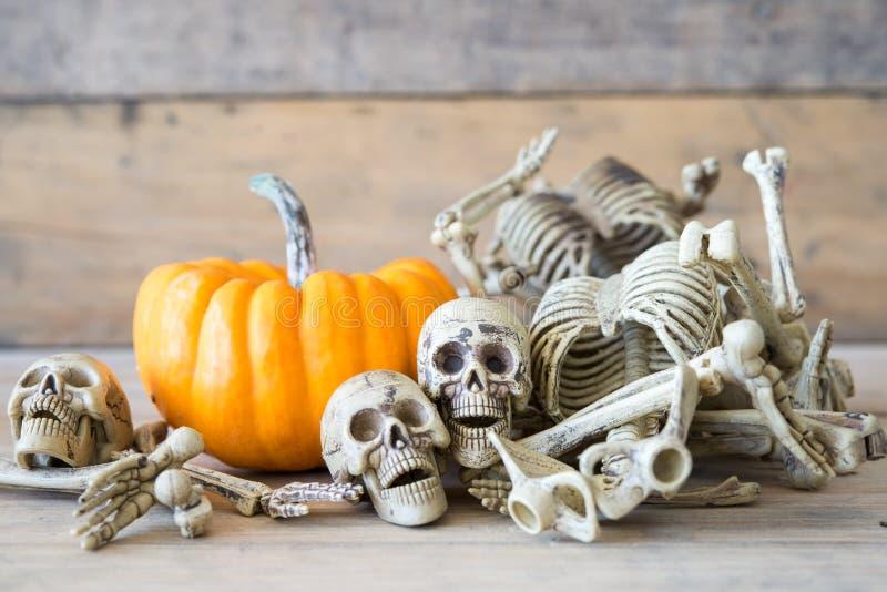 Cranio umano su fondo, sullo scheletro e sulla zucca di legno su legno, fondo felice di Halloween immagine stock libera da diritti