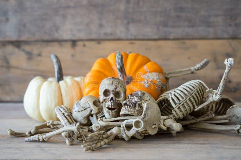 Cranio umano su fondo, sullo scheletro e sulla zucca di legno su legno, fondo felice di Halloween immagini stock libere da diritti